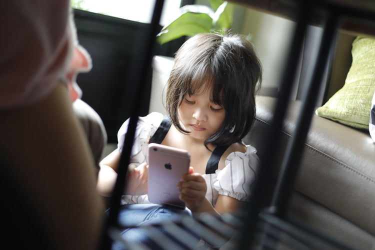 Boys Childhood Close-up Communication Day Family Girls Home Interior Indoors  Mobile Phone Playing Portable Information Device Real People Sitting Smart Phone Technology Togetherness Two People Wireless Technology