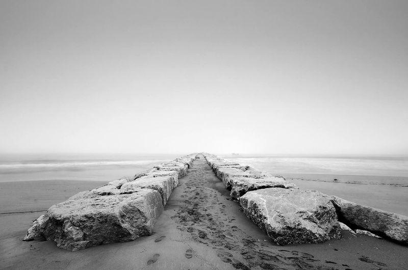 Groynes On Seashore Against Clear Sky