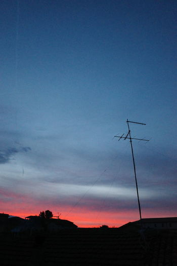 Low angle view of silhouette communications tower against sky at sunset