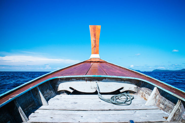 Boat moored on sea against blue sky