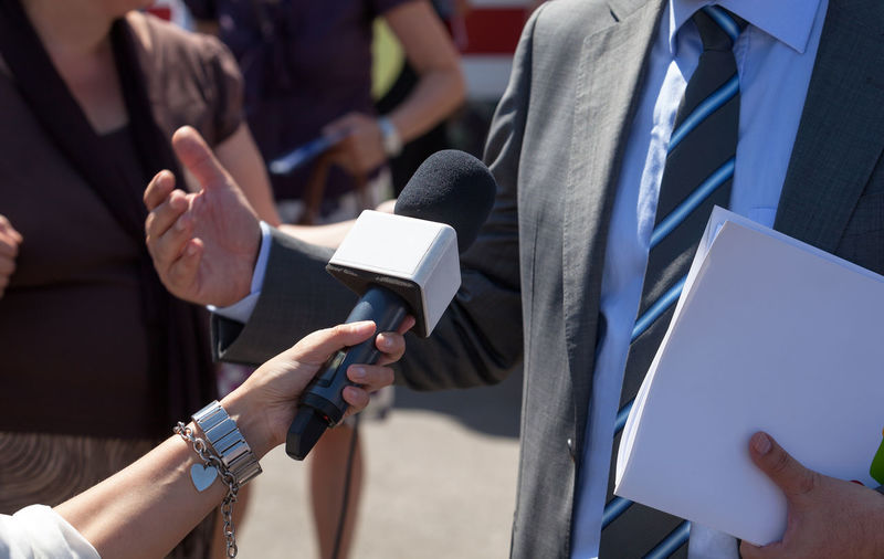 Cropped Hand Of Female Journalist Interviewing Businessman