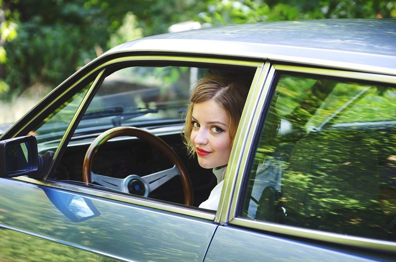 Smiling young woman looking through car window