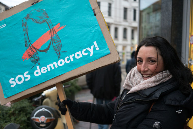 """Brussels, Belgium - December 7, 2017: Catalan female demonstrator holding up a banner reading """"SOS Democracy!"""" demanding independence for Catalonia Catalan Catalogne Catalonia Catalonia Is Not Spain Catalunya Democracy European Union Freedom Slogan Banner Catalans Cataluña Communication Demonstration Demonstrators Looking At Camera One Person Outdoors Real People Referendum"""