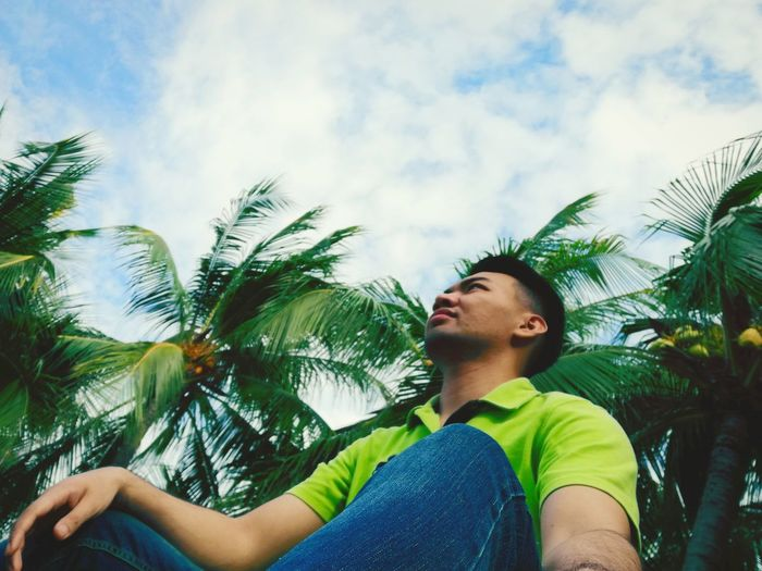 Low angle view of young man looking away against cloudy sky