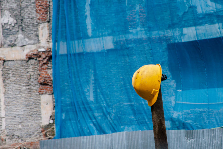 Yellow hardhat hanging on pole at construction site