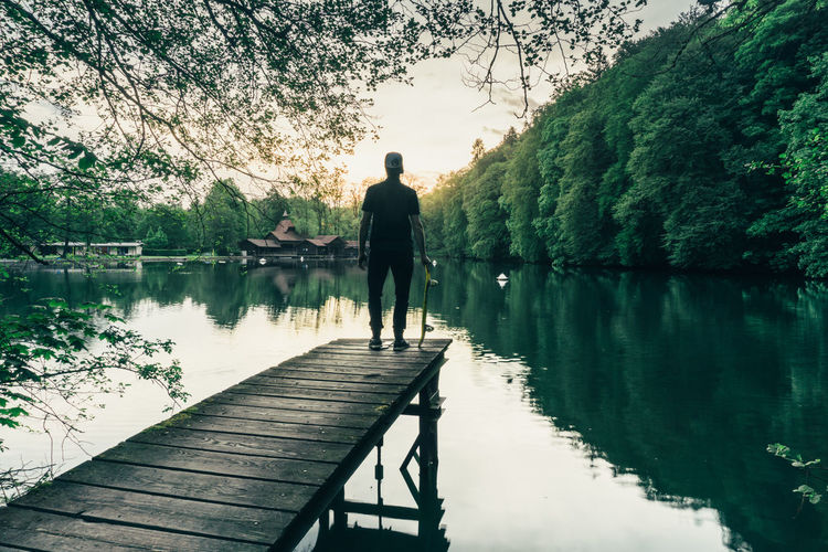 Rear view of boy with skateboard standing on pier over lake against trees