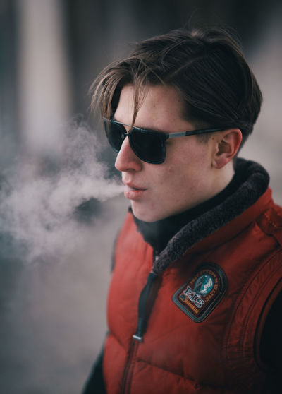 Young Man Wearing Sunglasses Smoking In Corridor