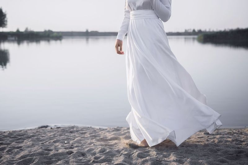 Low Section Of Woman Wearing White Dress Standing By Lake