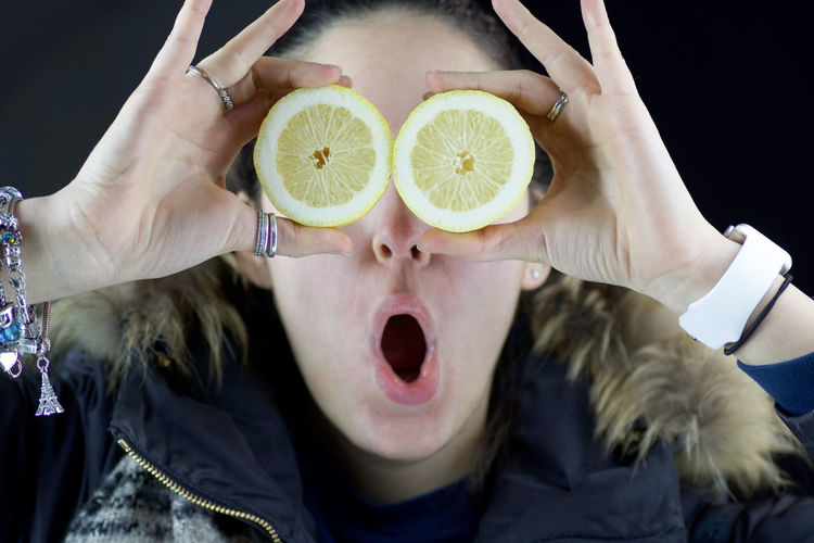 Close-up of woman holding lemon slices over eyes