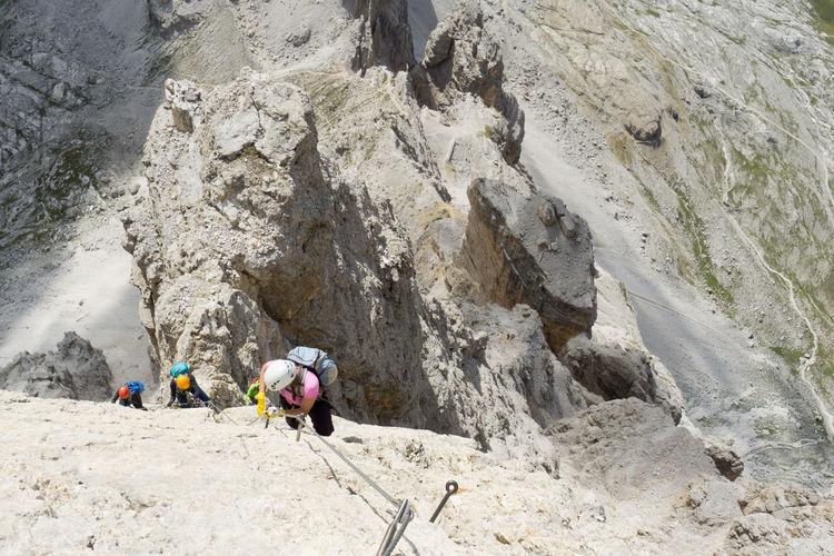 Rear view of people walking on rock formation