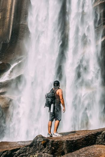 Man standing on rock looking at waterfall