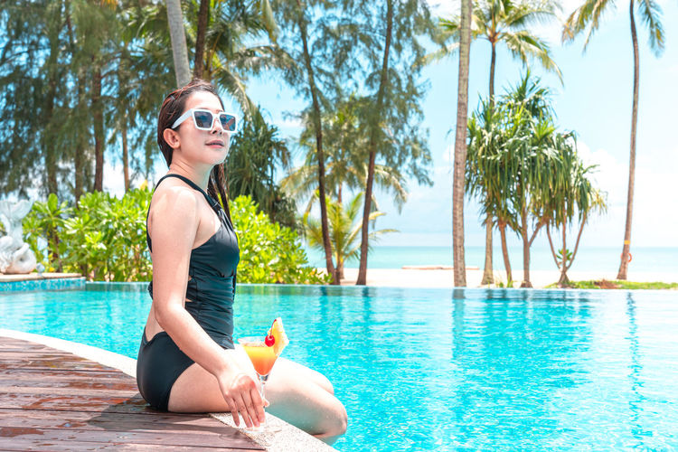 Young woman wearing sunglasses sitting on swimming pool