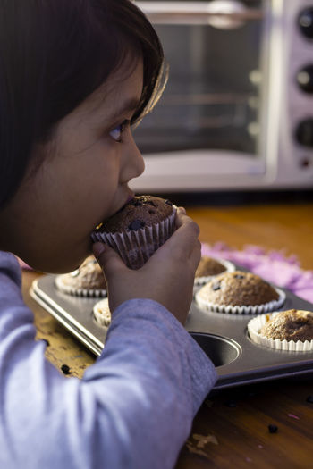 An indian girl child eating a homemade chocolate muffin cup cake baking tray with selective focus