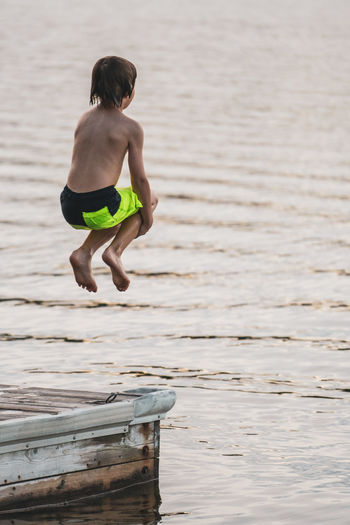 Young boy jumping off dock into lake in Northern Ontario. Swimming Wave Backgrounds Bathing Suit  Boy Child Childhood Day Directly Above Dock Heat Jumping Lake Leap Leisure Activity Nature One Person Outdoors Pier Play Shirtless Shorts Sky Water Waterfront Summer Sports Be Brave A New Beginning
