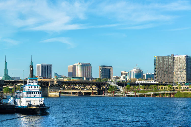 Beautiful waterfront view of Portland, Oregon and the Willamette River Architecture Boat Bridge Bridge - Man Made Structure Built Structure City Cityscape Day Downtown Oregon Outdoors Pacific Northwest  Portland River Sky Skyscraper Tourism Travel Travel Destinations Urban USA Water Waterfront Willamette Willamette River