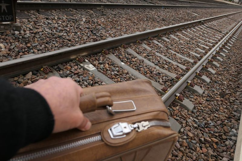 Cropped hand of person holding luggage at railroad station platform