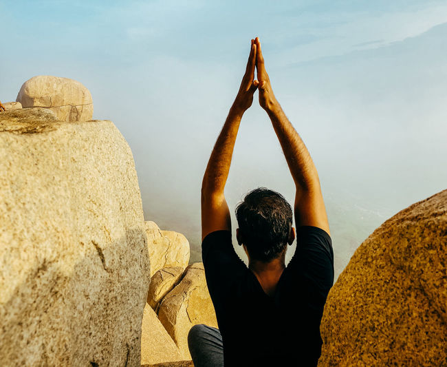 Rear view of man sitting on rock and doing yoga against sky