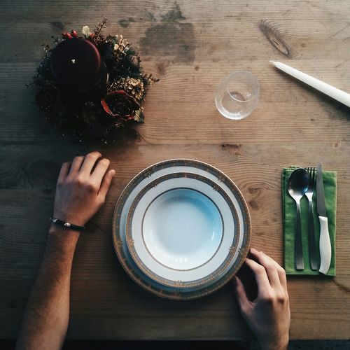 Hands and empty bowl on table
