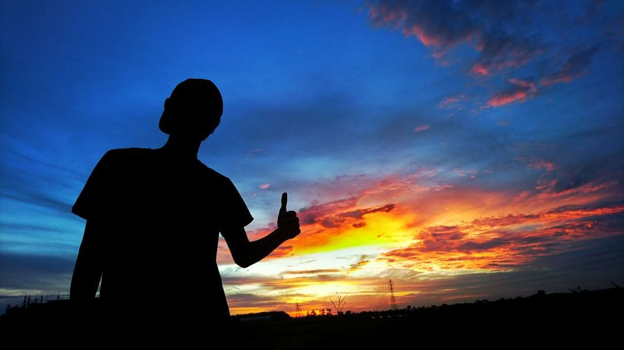 Low angle view of silhouette man showing thumbs up while standing against sky during sunset