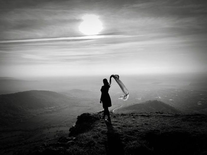 Monchrome photo of woman standing on top of the mountain holding a scarf floating in the wind