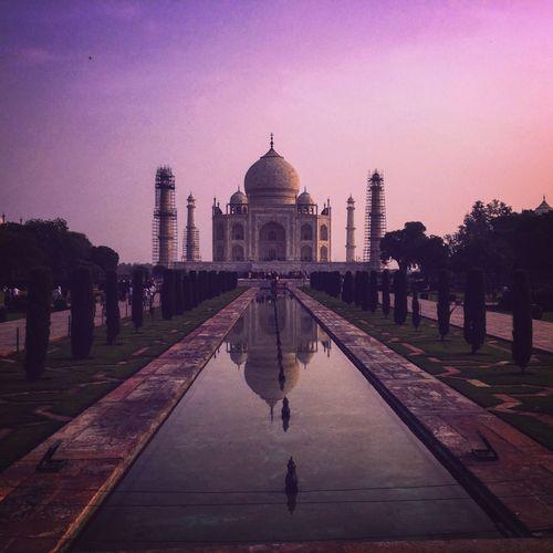 Reflecting Pool Towards Taj Mahal Against Sky During Sunset