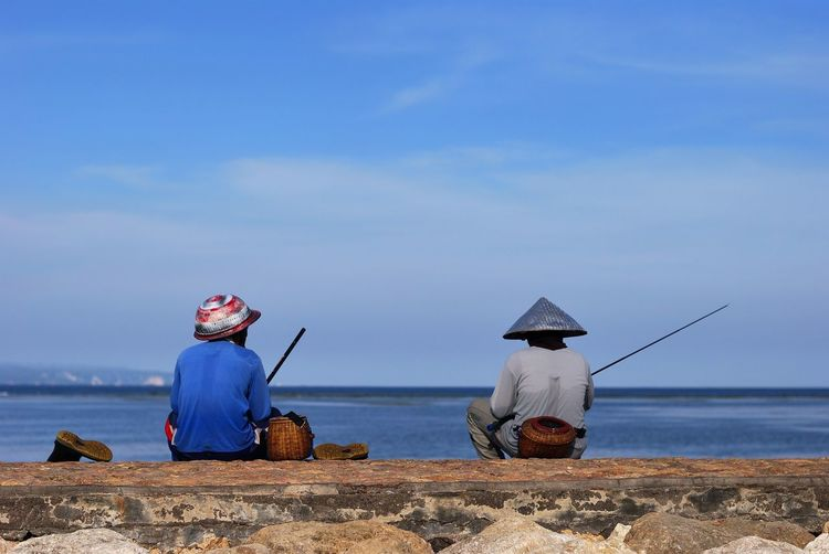 Rear View Of Men Fishing By Lake Against Sky