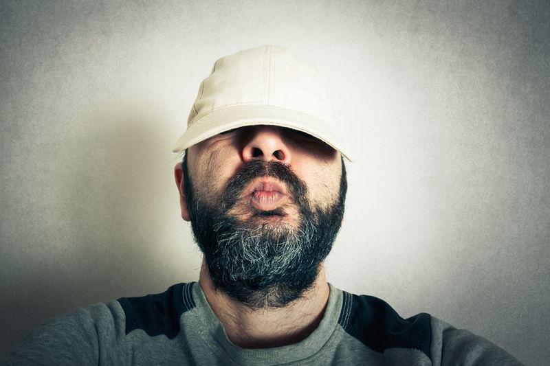 Portrait of man wearing hat against wall