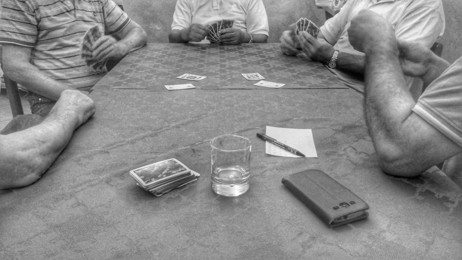 Mid section of men playing cards on table