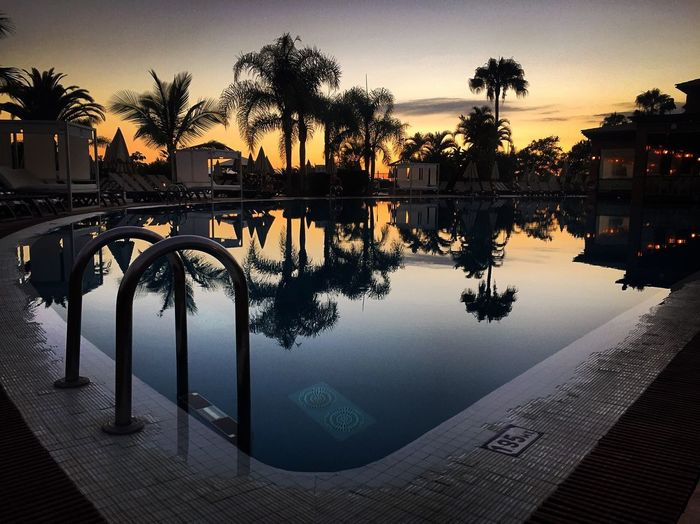 Scenic view of swimming pool by lake against sky during sunset