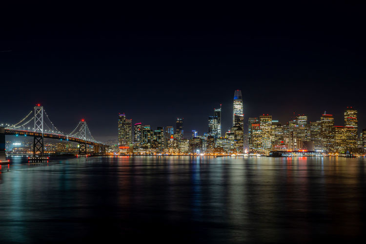 Urban skyline by river against sky at night