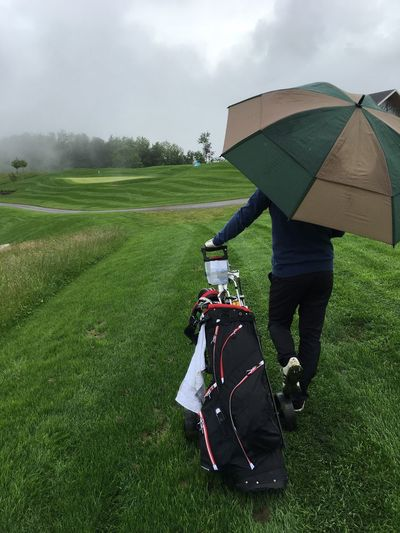 Rear view of golfer pulling golf bag on grass with umbrella against sky during rain