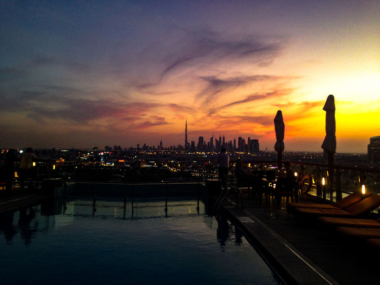 Enjoying a sundowner on the rooftop terrace at Dubai Hilton Blaue Stunde Built Structure Check This Out City Life City Skyline Cityscape Cloud - Sky Dramatic Sky Dubai Eyeemphoto Eyeemphotography Illuminated Intense Colors Modern Night View Outdoors Roof Terrace Skyscraper Sunset Swimming Pool Travel Destinations UAE Urban Skyline View Water