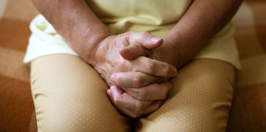 Hands of mature woman sitting on the couch