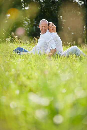 Side View Of Smiling Couple Sitting On Grassy Field