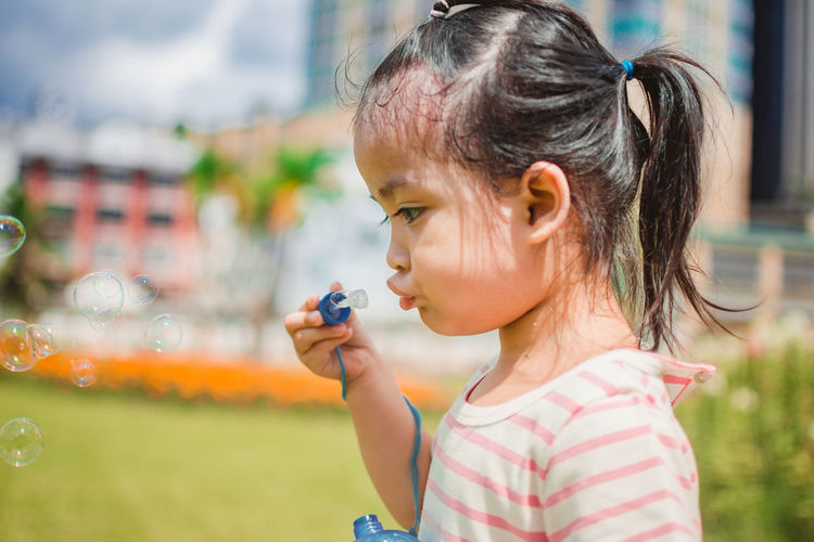 Girl blowing bubbles at park