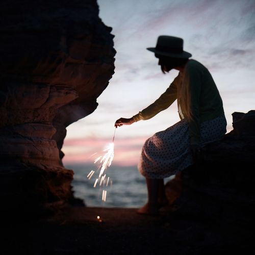 Full Length Of Woman Holding Sparkle While Sitting On Rock Against Sky During Sunset