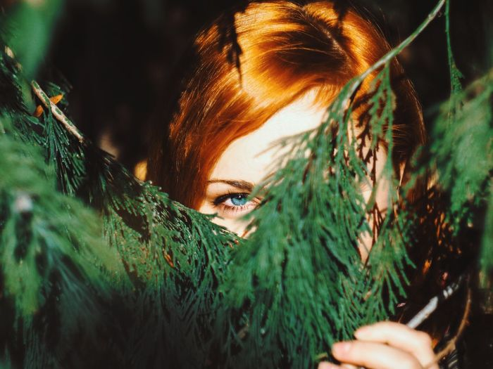 Through The Leaves Nature Close-up EyeEm Best Shots EyeEm Nature Lover EyeEm Selects Focus Human Hand Young Women Beautiful Woman Portrait Beauty Tree Women Beautiful People Human Face Headshot Dyed Red Hair Redhead Leaves Growing Woods Eyelash My Best Photo