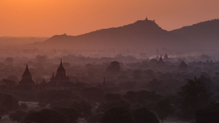 Panoramic view of temple and building against sky during sunset