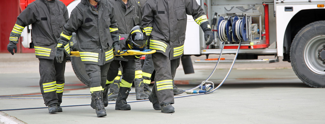 Low Section Of Firefighters Walking On Road