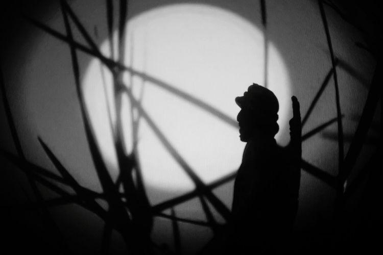 Silhouette man standing against wall at night