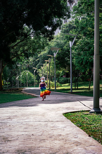 Man riding bicycle on footpath in park