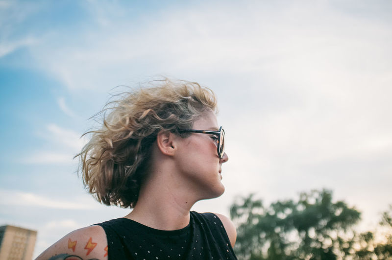 Mid adult woman wearing sunglasses while looking away against sky at sunset