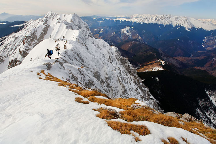 Low angle view of mountaineers climbing snowcapped mountain against sky