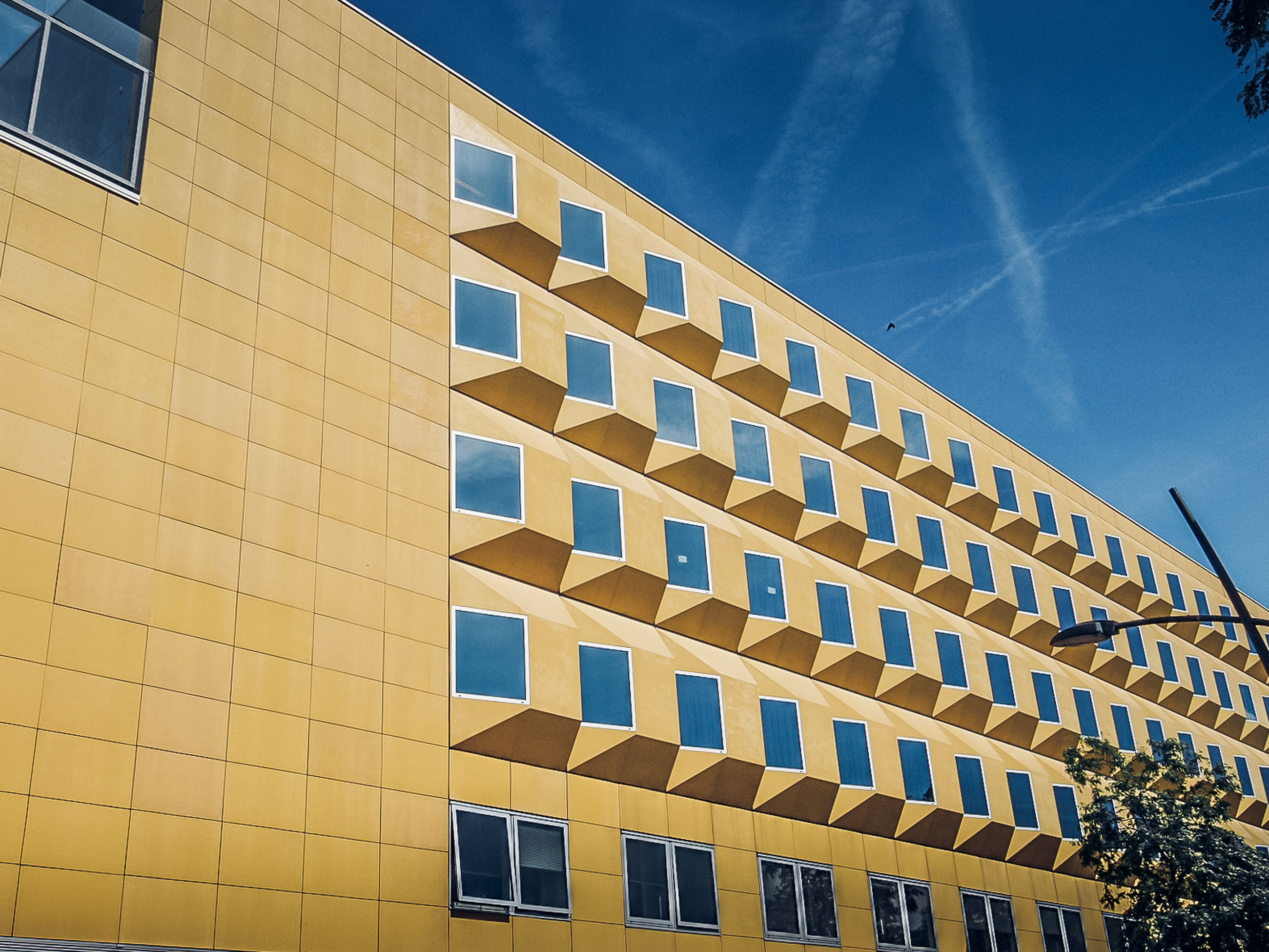 built structure, architecture, building exterior, sky, low angle view, building, window, cloud - sky, nature, sunlight, no people, day, blue, in a row, outdoors, city, pattern, modern, yellow, repetition, office building exterior