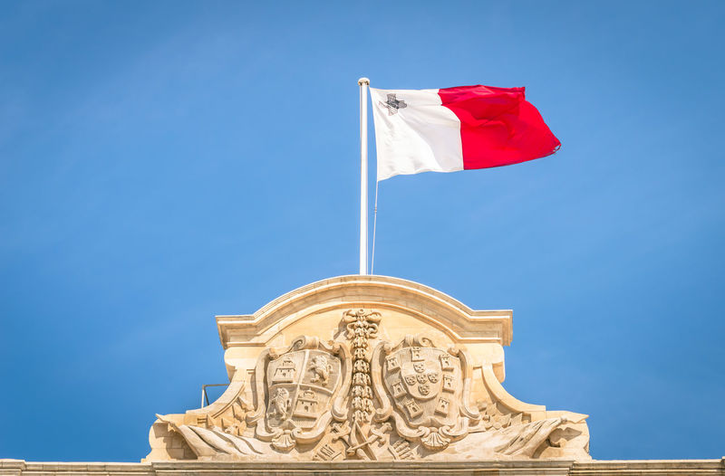 Low angle view of maltese flag on building against blue sky