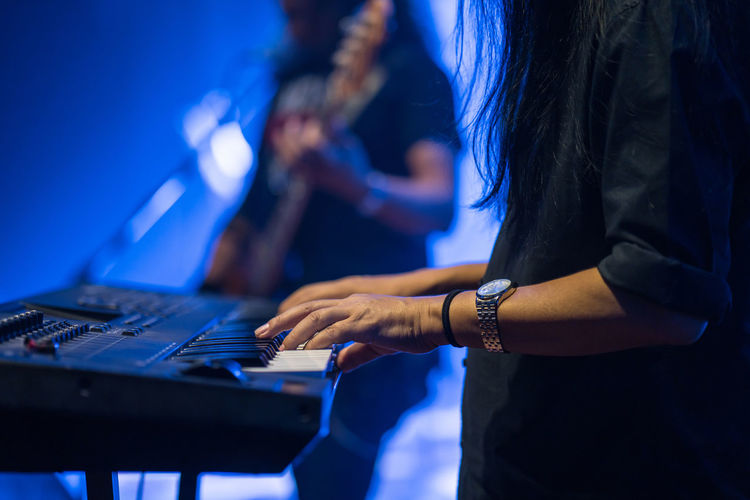 Pianist playing electric piano in concert at night, music concept. Jazz Music Piano Rock Show Blue Chord Concert Fingers Hand Keyboard Instrument Live Melody Performance Play Playing Synthesizer
