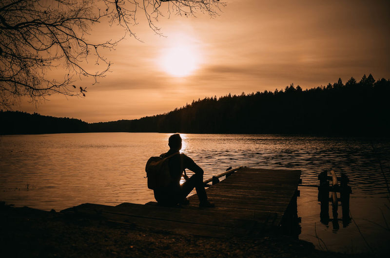 Silhouette man sitting by lake against sky during sunset