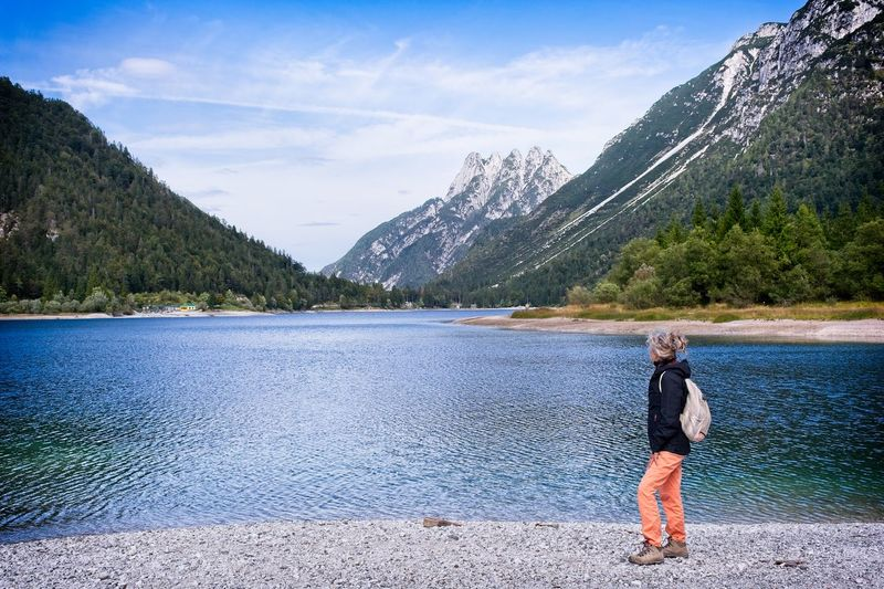 Boy on lake against sky