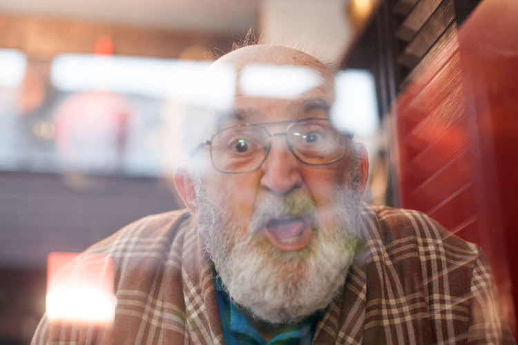 old man making funny face through window Background Bald Beard Casual Clothing Close-up Eyeglasses  Eyeglasses  Front View Funny Grimace Happy Headshot Indoors  Joking Lifestyles Man Neighbor Old Pajamas Pensioner Portrait Reflection Senior Adult Surprised Window