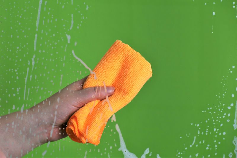 Cropped hand cleaning wet glass window with rag against green background